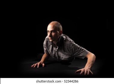 crawling man over dark background
