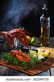 Crayfish with greens and a citrus on  table from old boards