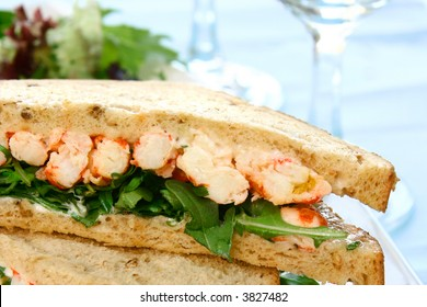 Crayfish and prawn sandwich with mayonaise and fresh rocket leaves on brown bread.