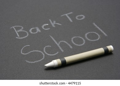 "Crayon writing on black background with words ""Back To School."""