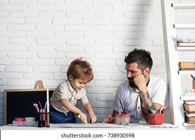Crayons drawing family, father looks how son draws. Development of motor skills and thinking in children garden, teacher and pedagogy, art therapy. Small artist paints with felt-tip pens and fingers