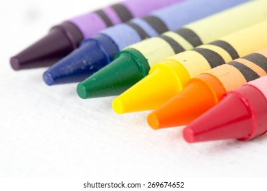 Crayons lined up on white.  They match the rainbow colors in order.