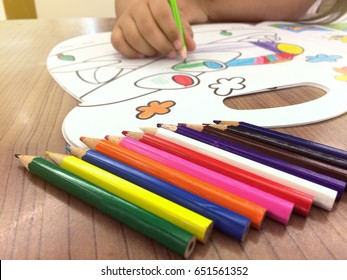 Crayons are placed on the table. And children's hand painting on paper (shallow DOF)