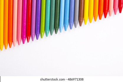 Crayons space background lined up isolated on white background with copy space