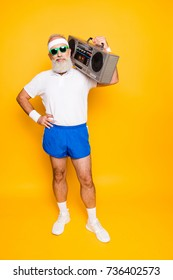 Crazy aged funny active sexy athlete pensioner grandpa in eyewear with bass clipping ghetto blaster recorder. Old school, swag, fooling around, gym, workout, technology, groove