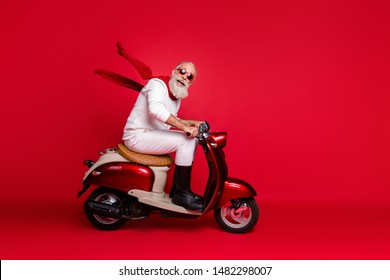 Crazy aged santa man coming newyear 2020 party by vintage moped wear jumper and trousers isolated red background
