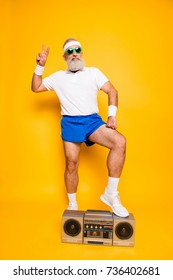 Crazy aged serious athlete pensioner grandpa in eyewear, sneakers, sexy shorts, with bass clipping ghetto blaster recorder. Old school, swag, fooling around, gym, workout, technology