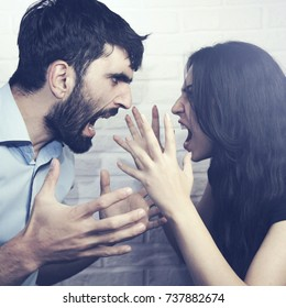 Crazy angry couple fighting hard on brick wall background
