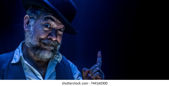 A crazy bearded man with bowler hat and vest signals to us inviting us to a Freak Show.