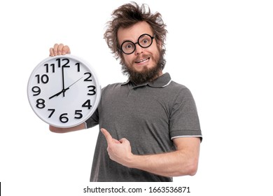 Crazy bearded Man with funny Haircut in eye Glasses holding Big Clock, isolated on white background. Time concept.