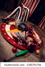 Crazy and beautiful female clown rotates somewhere on scene of dark circus arena