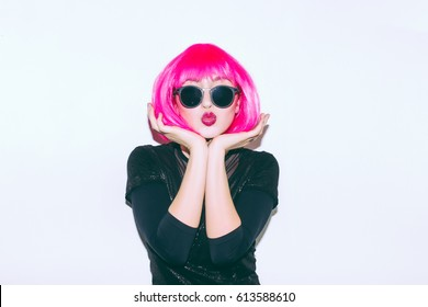 Crazy beautiful rock Girl in a acid bright pink wig and lama leather swag style red fur coat. Dangerous rocky party bored woman Ironically having fun. Flash style on white background color exclusive.
