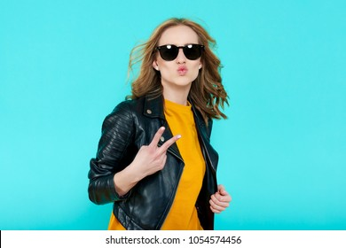 Crazy beautiful rock Girl in leather jacket and black sunglasses. Punk is not dead. Attractive cool young woman blowing a kiss and making peace sign hand gesture.