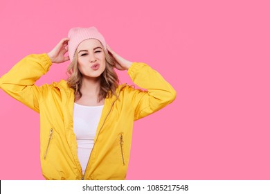 Crazy beautiful trendy girl in bright yellow jacket and pink beanie hat puckering lips. Attractive cool young woman fashion portrait over pastel pink background.
