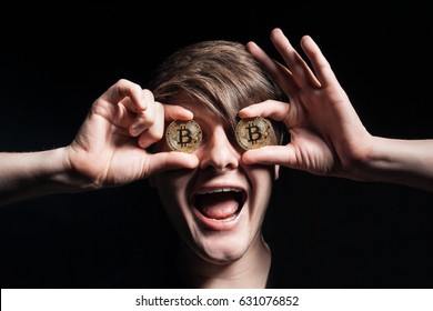 crazy bitcoin lover with golden coin by eyes; funny miner with btc near face;