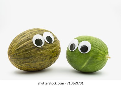 Crazy brown and green melon with googly eyes on white background