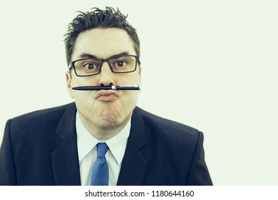Crazy business expert holding pen on lips and looking at camera. Concentrated handsome businessman in eyeglasses wasting time and balancing pen on upper lip. Boredom concept
