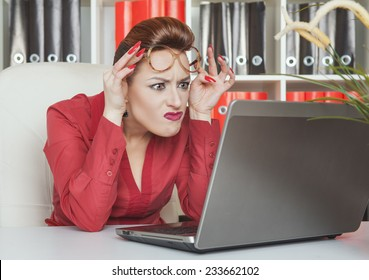 Crazy business woman in glasses working with laptop