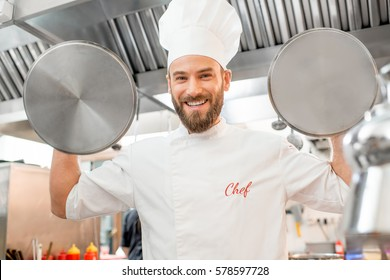 Crazy chef cook holding pan covers at the restaurant kitchen
