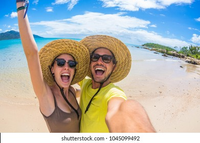 Crazy couple in love having fun taking a selfie at a tropical beach at holiday