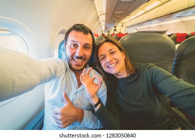 crazy couple take selfie on the airplane during flight before landing.They are a man and a woman, smiling and looking at smartphone. Travel, happiness and lifestyle concepts.