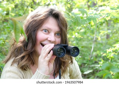 crazy curious european adult woman close-up, holding black field binoculars with zoom, hiding in greenery, peeping from green bushes, spying on unfaithful husband, neighbors