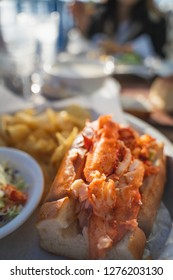 crazy delicious lobster roll from half moon bay renown restaurant along the bay with sunlight ocean and on the pier from the side open faced sandwich mouthwatering and ready to eat with clam chowder
