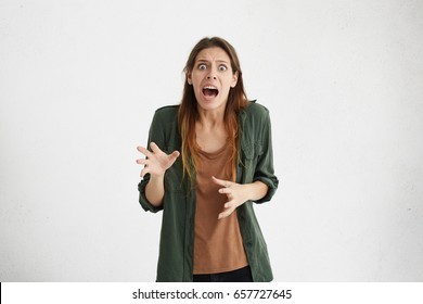 Crazy desperate woman being shocked looking at camera with wide opened mouth and bugged eyes screaming with horror. Mad anxious female trembling with fear. Negative emotions and feelings concept