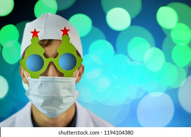 Crazy doctor in Christmas tree glasses and white coat on blue background with bright green lights. Copy space for text. Merry Christmas Doctor