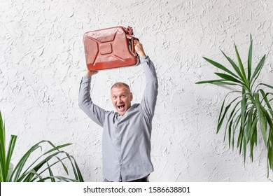 Crazy emotional young man holds over the old head canister posing in a bright cozy room. Funny man holds a gas canister over his head and screams. Place for text