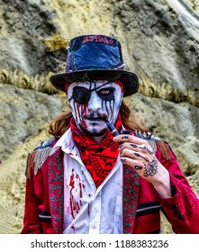 Crazy evil bandit robber pirate man stained in blood is smoking a tube. Halloween. Horror
