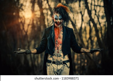 Crazy evil clown man is standing in the forest. Halloween. Horror, thriller movie.
