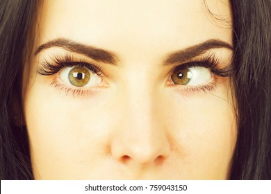 crazy female eyes with strabismus of pretty woman or cute girl at optician with mad, comic or surprised face, closeup