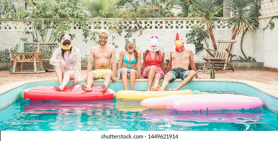 Crazy friends having fun wearing and party masks sitting next swimming pool - Young trendy people enjoy summer time in rented villa - Travel, friendship, youth and tropical concept - Focus on faces