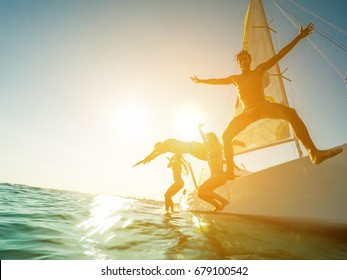 Crazy friends jumping off the boat into the ocean - Young happy people having fun diving into the sea - Travel, tropical, summer and concept - Soft focus on left man face - Tilted horizon composition