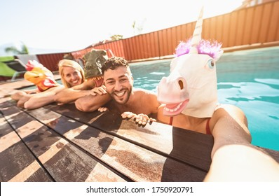 Crazy friends selfie doing pool party wearing bizarre mask - Young people having fun celebrating summer in exclusive tropical resort - Friendship and youth holidays lifestyle concept