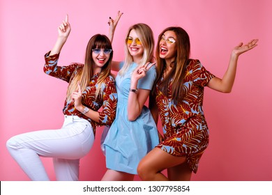 Crazy funny picture of three happy best friends girls enjoying party time together, dancing and laughing, color matching trendy elegant outfits and glasses, positive mood, pink background.