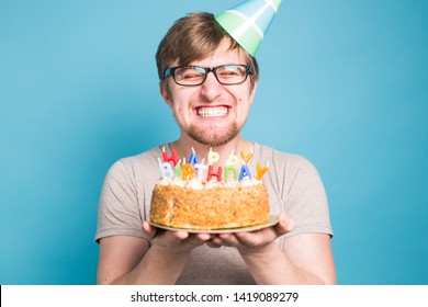 Crazy funny young man in glasses and paper congratulatory hats holding cakes happy birthday standing on a blue background.