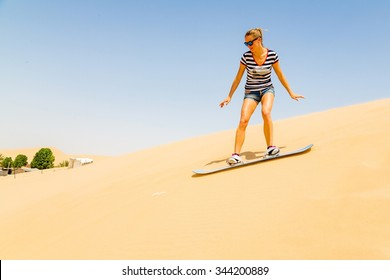 Crazy girl sand boarding down the dunes in the middle of a desert
