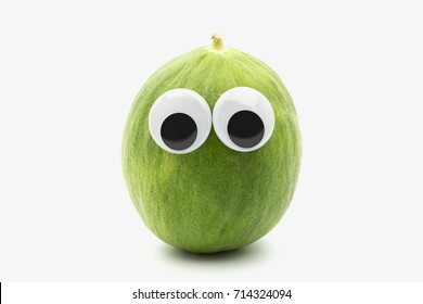 Crazy green melon with googly eyes on white background - the Barattiere is a variety of melon cultivated in Apulia, Italy