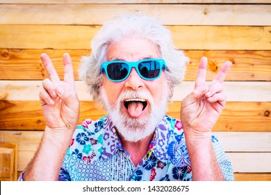 Crazy and happy active young and youth senior man making fun expression at the camera with winner hands - white hair and no limit age for old people love to play - happiness lifestyle for retired