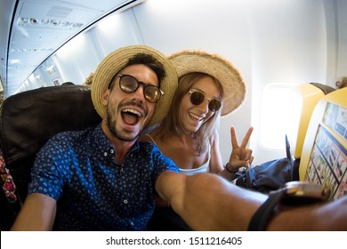 Crazy and happy couple take selfie on the airplane during flight. Concept about travel, lifestyle and happiness