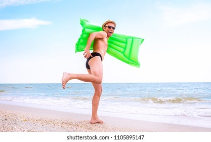 Crazy happy man with swimming mattress runs in the sea