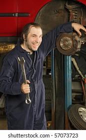 A crazy happy mechanic fixing brakes.