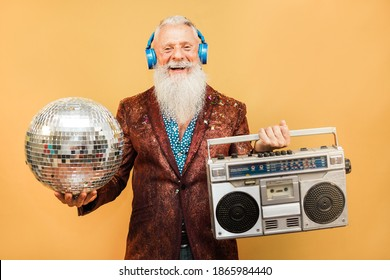 Crazy hipster man listening music with headphones while holding disco ball and vintage stereo - Party concept - Shutterstock ID 1865984440