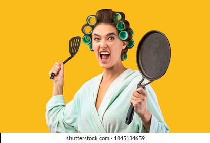 Crazy Housewife. Angry Woman Raising Frying Pan Threatening And Screaming Posing Looking At Camera Standing Over Yellow Studio Background. Furious Wife Shouting Tired Of Cooking Concept