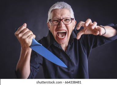 Crazy insane senior woman with a kitchen knife about to kill someone, furious and mad