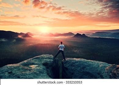 Crazy jumping hiker in black celebrate triumph between two rocky peaks. Wonderful daybreak.