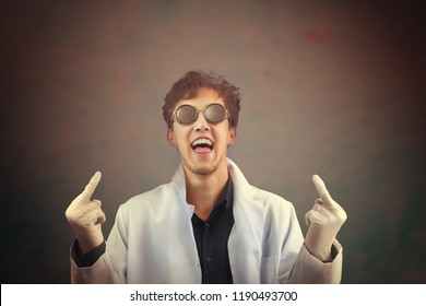 Crazy laughing man doctor in white coat and sunglasses giving you fingers in the center. Flipping off the middle finger bird gesture on dark background. The hands is selectively in focus. Halloween