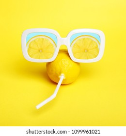 Crazy lemon with a straw in white sunglasses with lemon slices reflection. Minimal  beauty & fashion summer mood concept. Trendy bright colors.